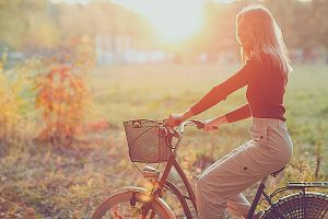 smiling young woman riding vintage bicycle in autumn park at sunset