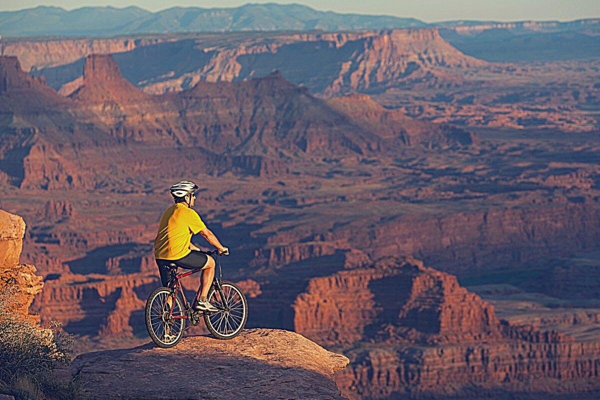 male cyclist sitting on bicycle looking at the view of Canyonlands National Park, Moab, Utah
