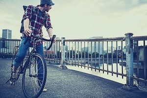 a young man commuting in an urban city environment on his drop bar road bike