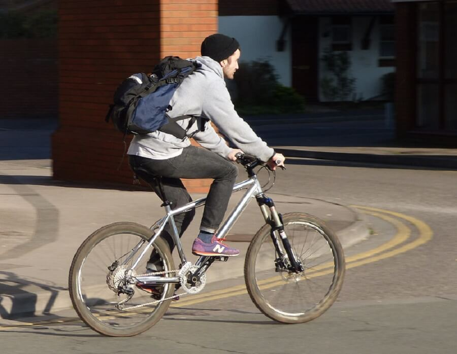 cyclist with backpack and hat biking on the road in the morning - Flickr image