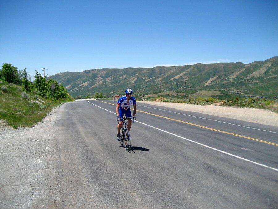 male cyclist biking on the road going uphill Emigration Canyon - Flickr image