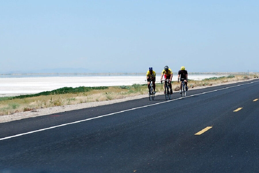 three adult cyclists biking on the road of Antelope Island, Utah on sunny day - Flickr image