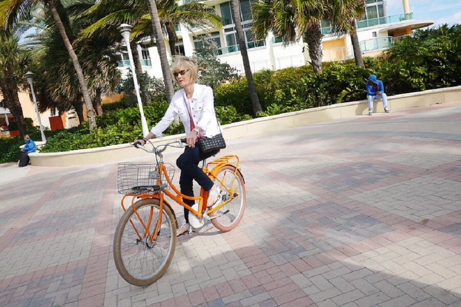 woman in orange bicycle cycling in the morning around South Beach Trail - Flickr image