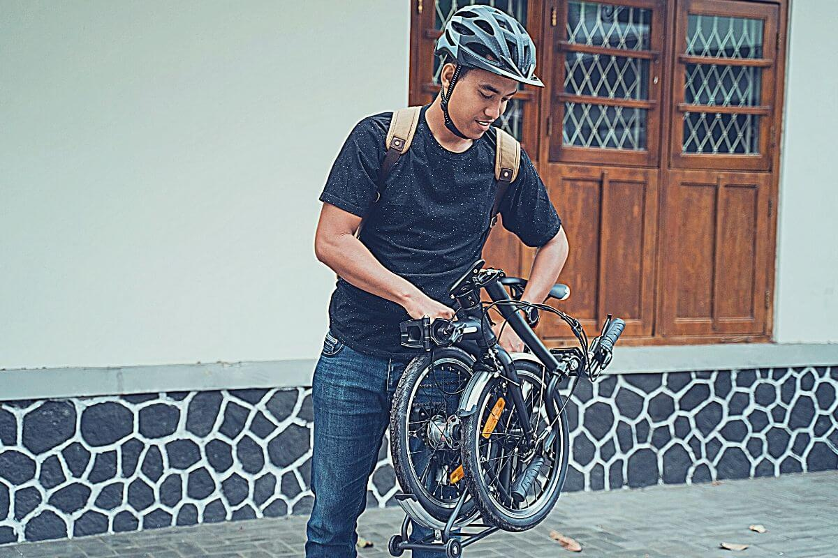 asian young man preparing his folding bike in front of the house
