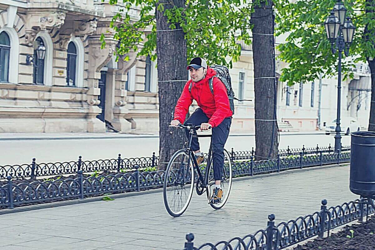 Young guy riding bike in a city with possessions