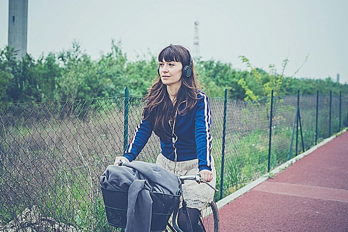Woman bike commuter riding on bike wearing headphones