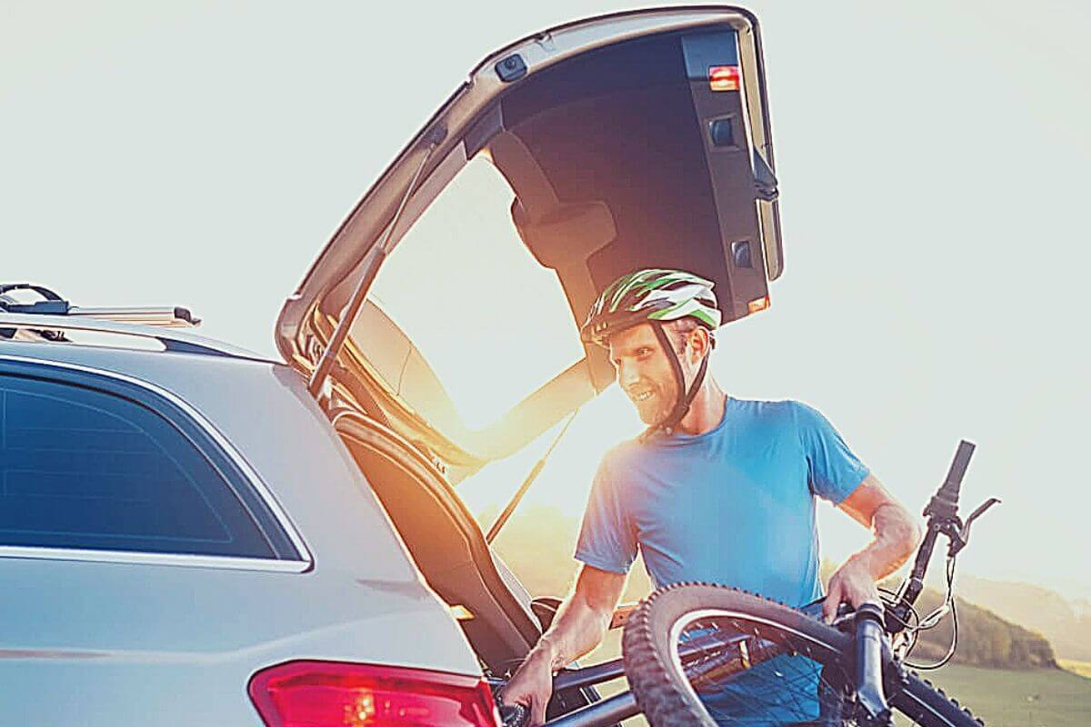 Man putting his bike into the trunk of a car