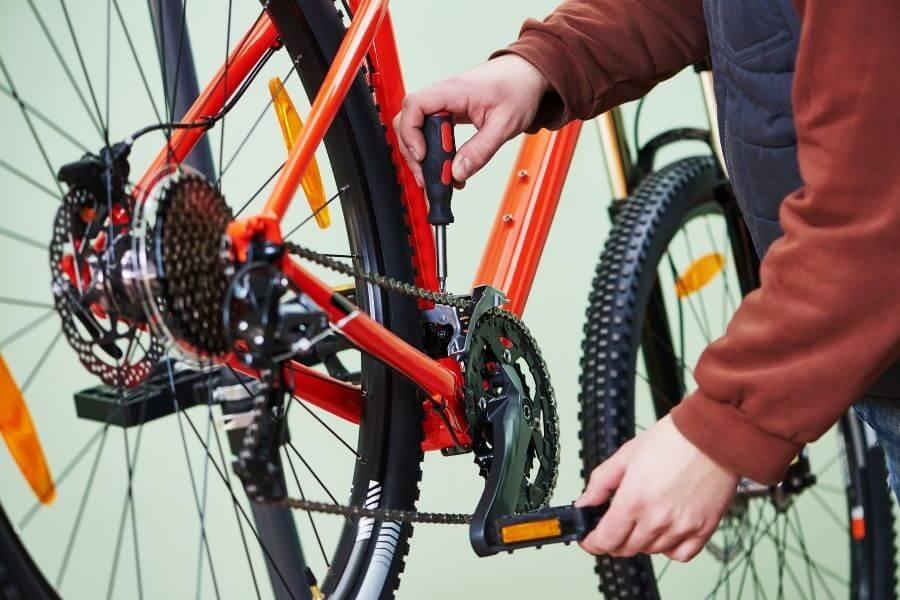 Bike repairman assembling and adjusting bike chain for maintenance