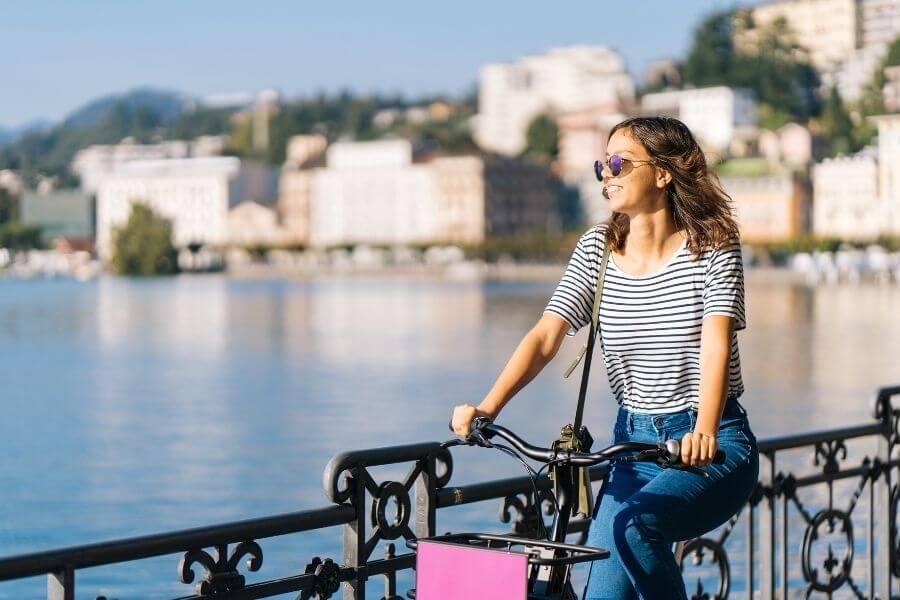 Cheerful female commuter riding on bike enjoying the scenery