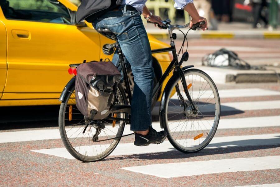 Male bike commuter on pedestrian holding a brake