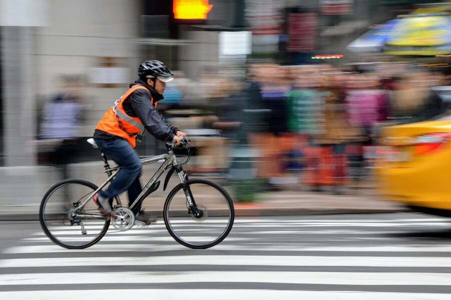 Man riding a bicycle wearing bright neon orange reflector vest