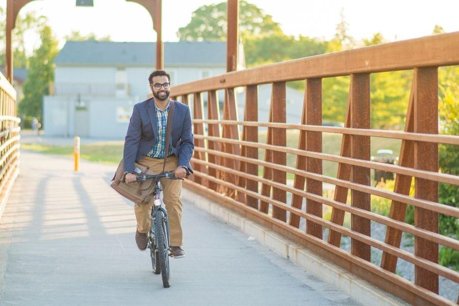 Happy office employee riding a bike on bridge commuting to work