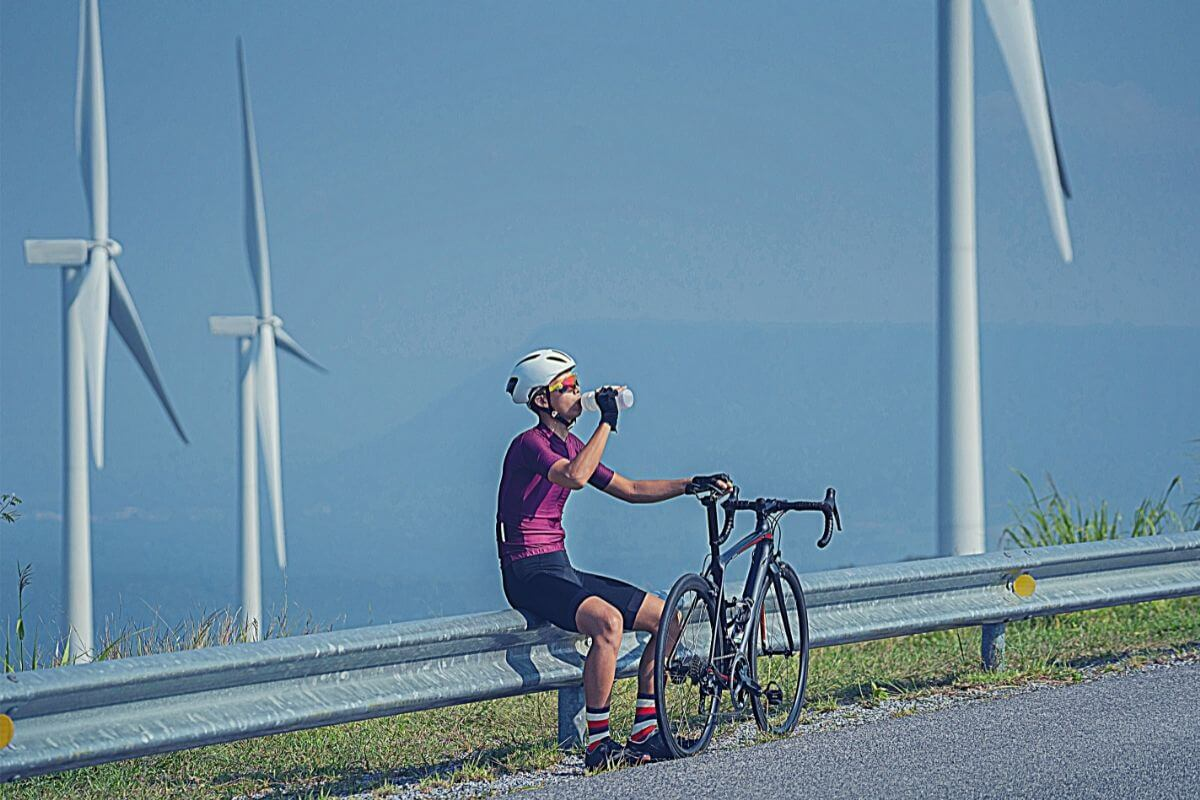 male cyclist drinking from water bottle while sitting on roadside in hot weather