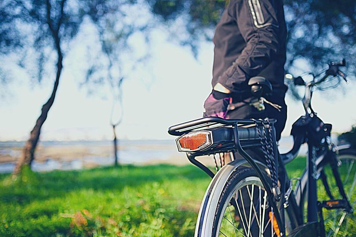 commuter standing beside an e-bike with rack installed