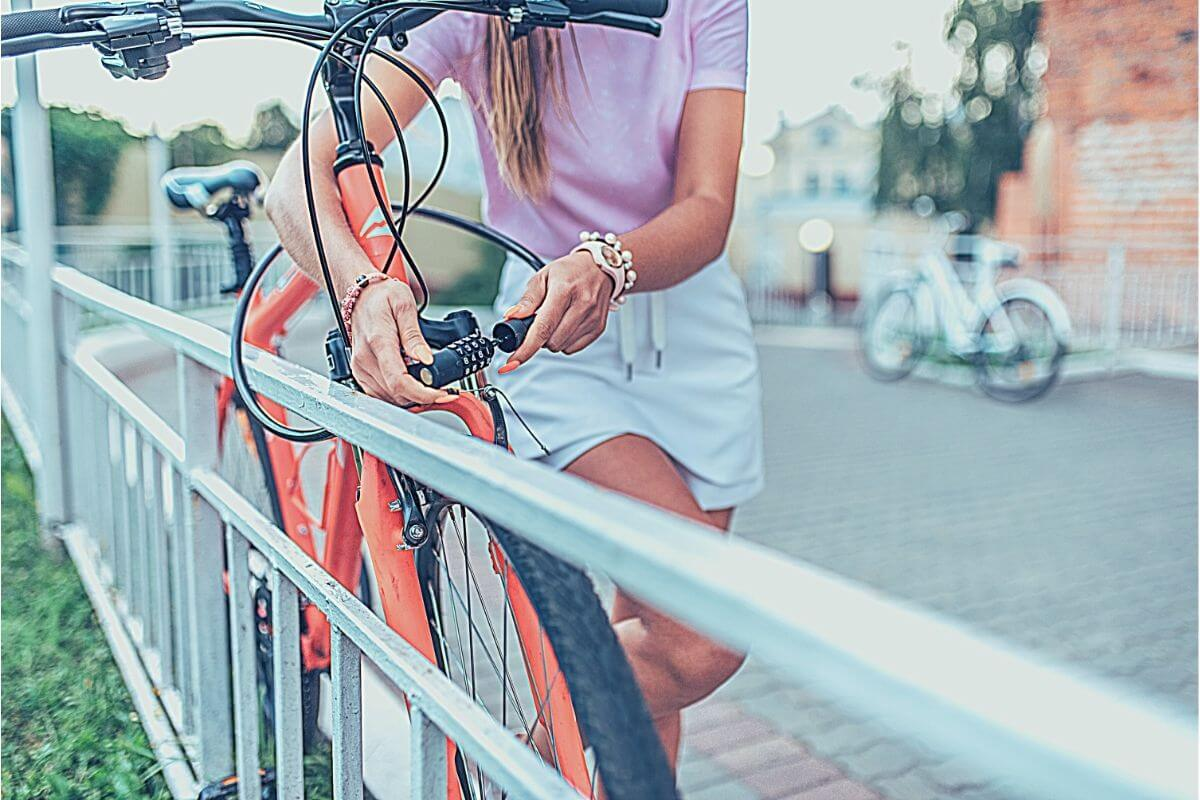 female commuter standing on side of the park locking her bike