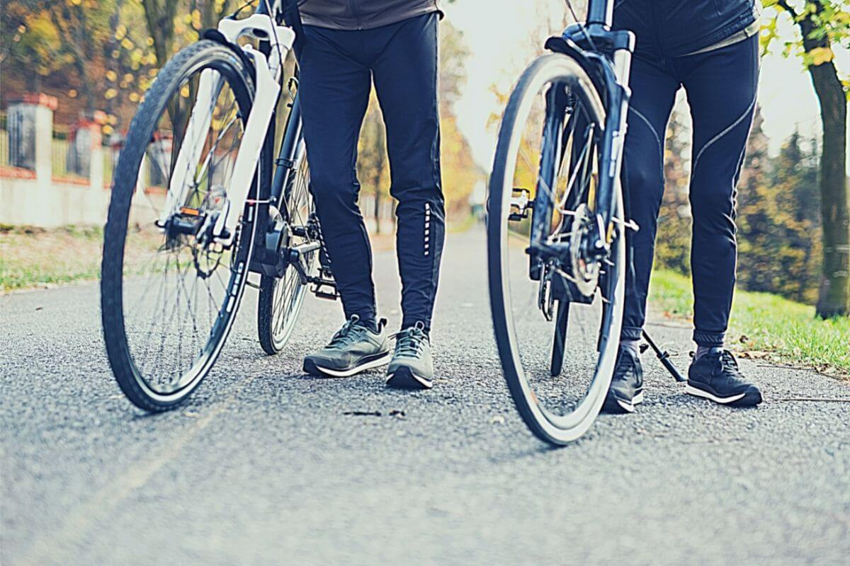 Two bike commuters wearing black cycling shoes standing on the road