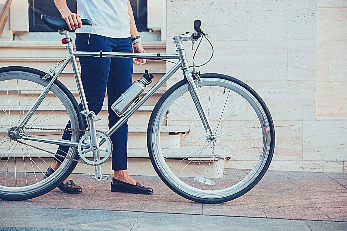 Female bike commuter standing while holding her bike