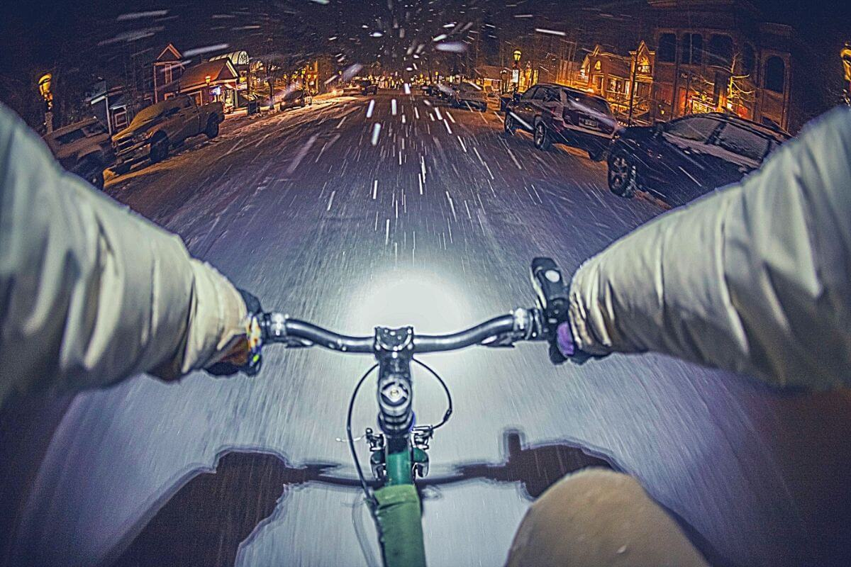 Cyclist biking in snow on the road during winter
