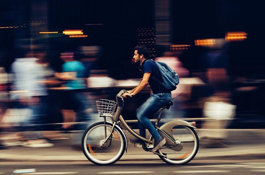 Man riding a rental bike through a city