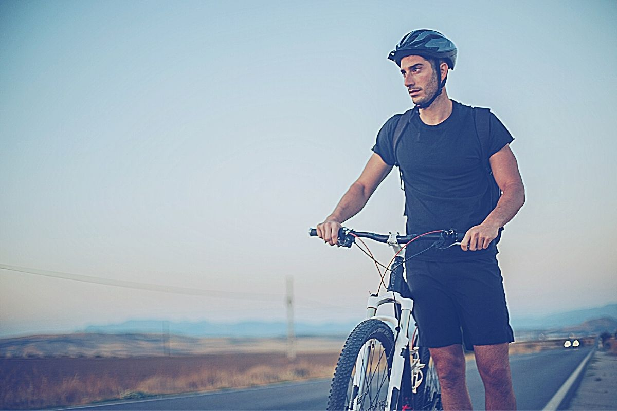 Male commuter in black shorts and helmet standing on roadside holding his bike
