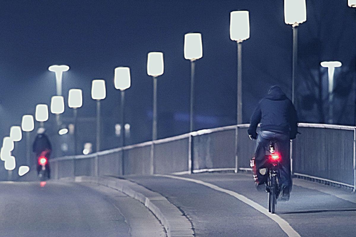 Men commuting by bike at night
