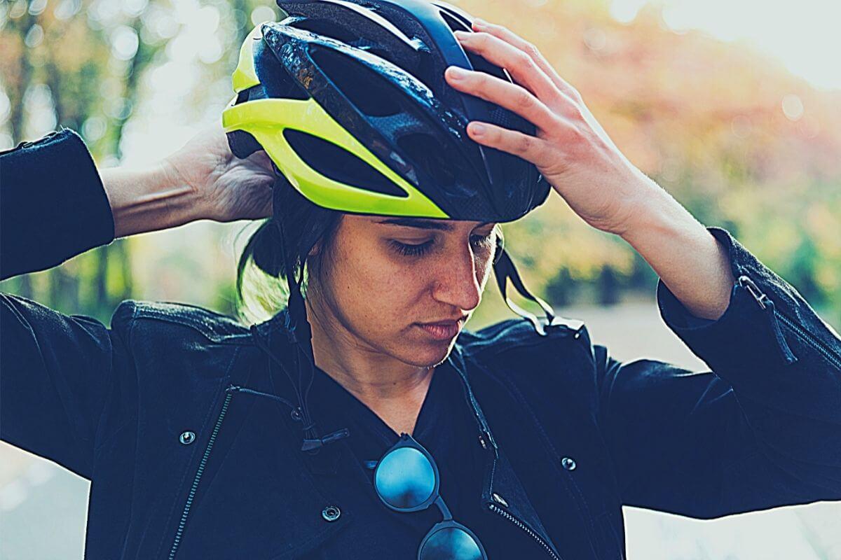 Female cyclist putting bike helmet on