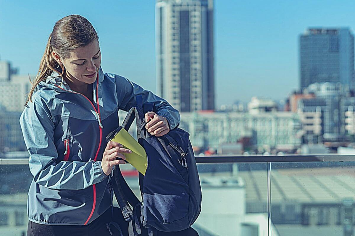 Female bike commuter packing thermos in backpack