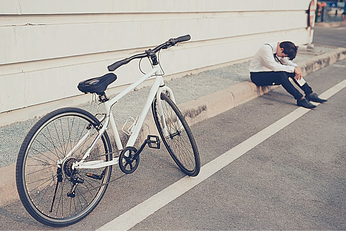 Male bike commuter on roadside feeling very tired and demotivated