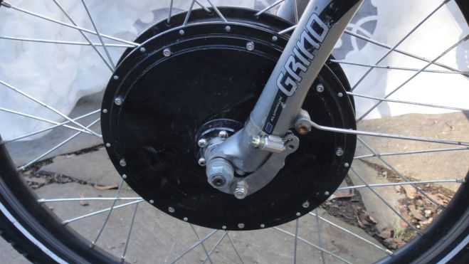 """Thea's motor is a Nine Continents direct drive hub kit from E-BikeKit.com for about $500. There are a lot of ebike kits out there but E-BikeKit is especially dedicated to excellent service. You'll notice that I had to file off the """"lawyer lips"""" around the dropouts in order to get the hub motor axle nuts to seat properly. Grin Cyclery's excellent troubleshooting page tell s how omitting this step may lead to front fork failure."""