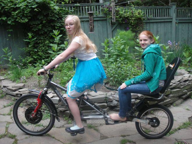 Thea and JJ model the passenger bike prototype.