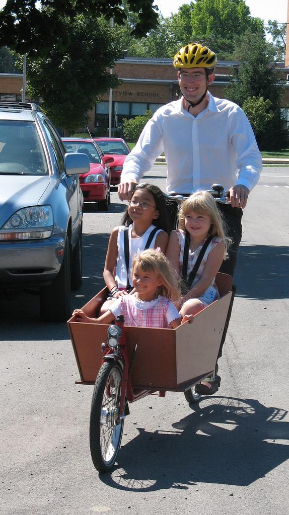 Three children in a bakfiets cargo bike