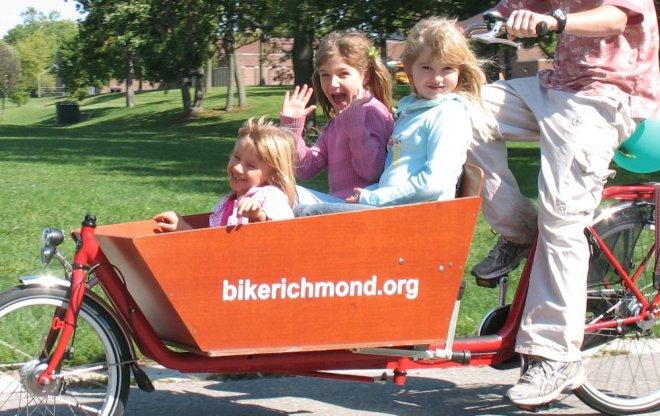 three happy girls in a cargo bike
