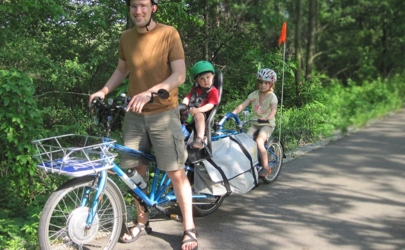 father rides cargo bike with two kids