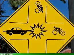 Fake traffic sign showing car/bike collision at four-way intersection