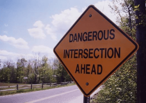 Road sign that reads Dangerous Intersection Ahead