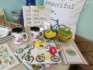 "Pillow, coffee cups, dish towels, and other items with images of colorful bicycles and the saying ""Life is a beautiful ride."""