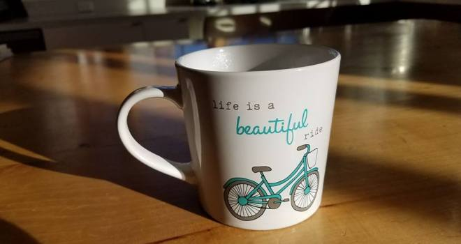 "In foreground, sitting on a wooden table-top in soft lighting, white coffee cup with drawing of a turquoise upright bicycle and the words ""Life is a beautiful ride"". Background soft focus of kitchen with appliances."
