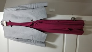 Outfit hanging on a white door: Light gray fitted jacket with one button, straight slit pockets, Mandarin collar, over a scarlet silky wrap dress.
