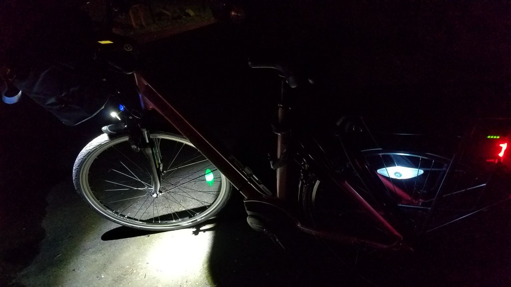 A bicycle in the dark with a headlight, tail light, and lights on the spokes all on.