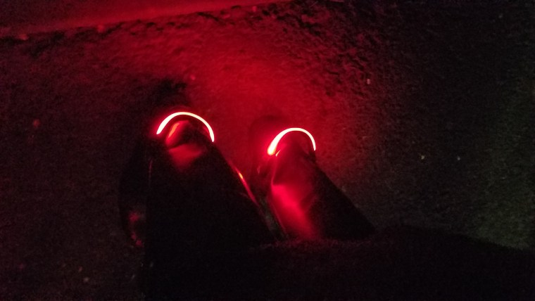 Dark night with glowing red lighted bands in a semi-circle on the heels of a pair of boots.