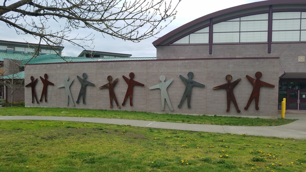 Side of an elementary school building with playful appliques of stylized human bodies holding their arms straight out, in various colors of metal (light gray, silver, darker bronze/brown). Grassy lawn in front of the wall with a paved path.