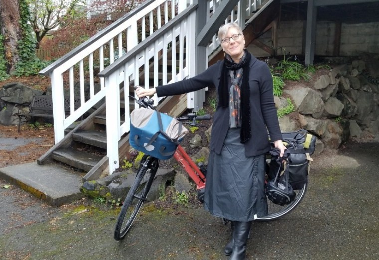 White woman standing with peach-colored e-bike at the foot of stairs with a white railing. Bike has light blue and silver bag on the front. woman wearing black jacket, black rain skirt, black boots, scarf with a few bronze leaves on it around her next. Short blonde hair, blue glasses, head tilted to her right, smiling, holding bike helmet, hand outstretched to hold the bike's handlebars. rock wall visible behind at right.