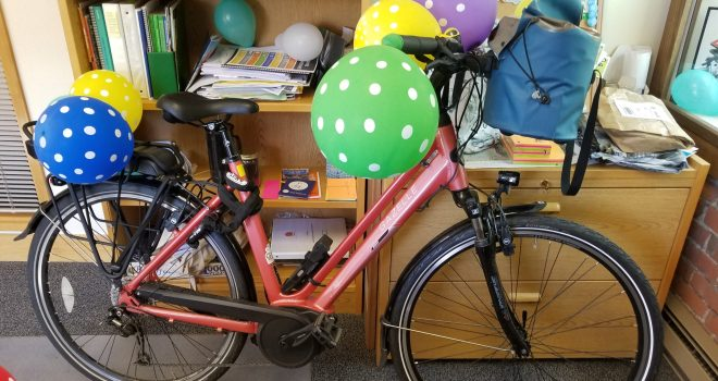 Peach-colored Gazelle Medeo e-bike in an office with polka-dot balloons attached to handlebars and back rack.