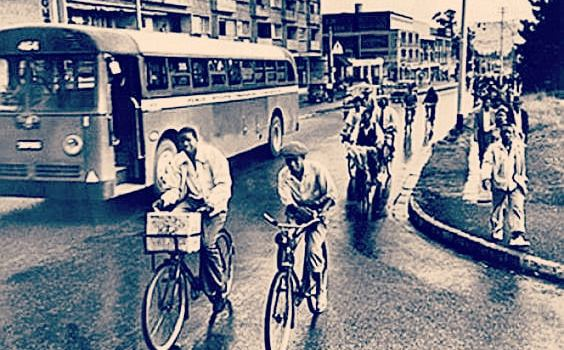 Black and white image showing bus at left, African American riding bicycles and walking at right, during the Montgomery bus boycott.