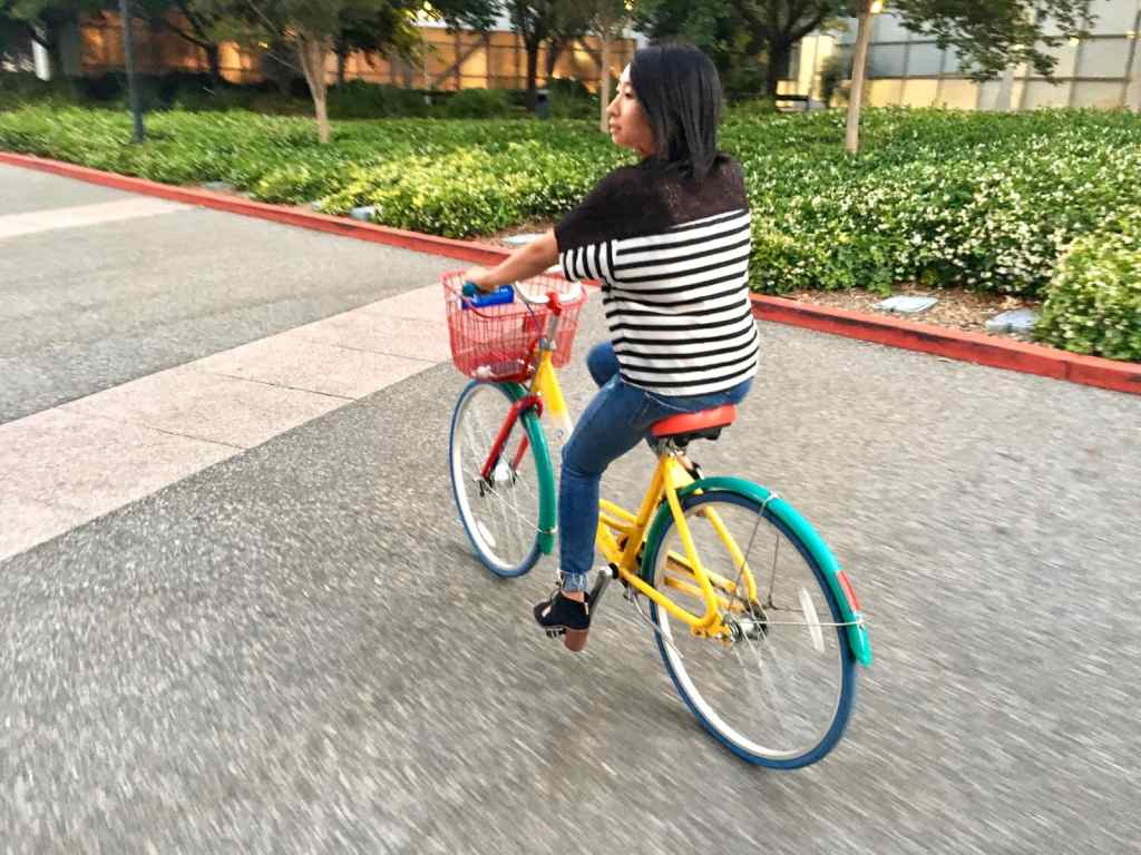 Riding a google bike in mountain view in heels while looking behind her on a bicycle.