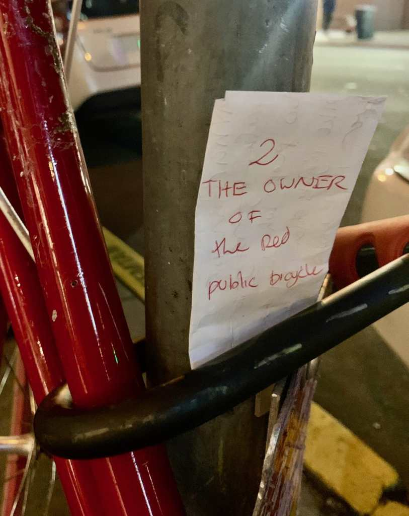 """A note tucked into my U-lock that has written on it: """"2 the owner of the red public bicycle"""""""