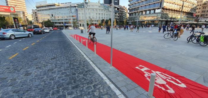 Someone riding on a red carpet showing where the bike lane should be. In this case a sidewalk lane.