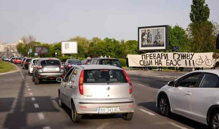 A traffic jam in Serbia with bike advocates holding signs.