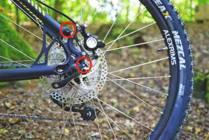 A close up on a rear hub of a mountain bike with different eyelets for a frame mount, one above and one to the side of the disc brake mechanism.