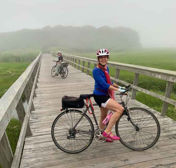two people biking with rear racks and trunk bags on top of the rear racks on a bike trail in cape cod, Massachusetts